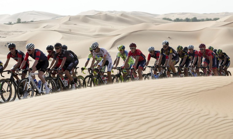 The pack pedals along desert dunes, during the first stage of the Abu Dhabi tour cycling race, from Qasr Al Sarab to Madinat Zayed, UAE, Thursday, Oct. 8, 2015. (Claudio Peri/ANSA via AP)