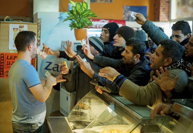 Migrants try to buy some food at a takeaway after they crossed the Austrian-Slovenian border in Spielfeld, Austria, Wednesday, Oct 21, 2015. Thousands of people are trying to reach central and northern Europe via the Balkans but often have to wait for days in mud and rain at the Serbian, Croatian and Slovenian borders. (AP Photo/Christian Bruna)
