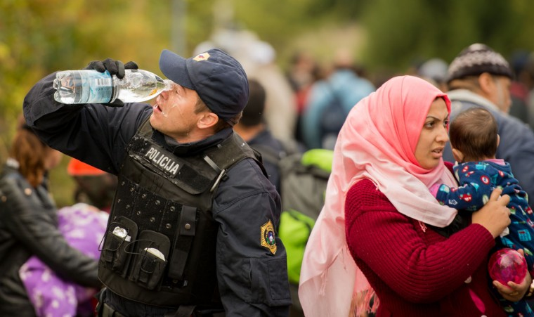 A Slovenian police officer cleans his eyes after Slovenian police used pepper spray as a group of migrants attempted to break through a cordon in a makeshift camp near the Austrian - Slovenian border in Sentilj, Slovenia, Tuesday, Oct 20, 2015. Thousands of people are trying to reach central and northern Europe via the Balkans but often have to wait for days in mud and rain at the Serbian, Croatian and Slovenian borders. (AP Photo/Christian Bruna)