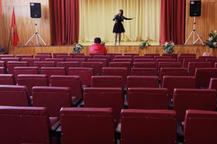 A woman listens to a singer during a concert at a polling station during the presidential election in the village of Smilovichi, 48 km (30 miles) east of Minsk, Belarus, Sunday, Oct. 11, 2015. A presidential election was under way Sunday in Belarus, where authoritarian leader Alexander Lukashenko faced no serious competition and was expected easily to win a fifth term. The opposition called for a boycott of the vote. (AP Photo/Dmitry Lovetsky)