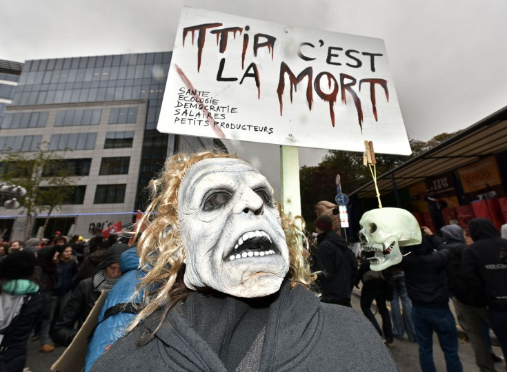 """A protestor with a mask demonstrates against the free trade agreement TTIP (Transatlantic Trade and Investment Partnership) during an EU summit in Brussels, Belgium on Thursday, Oct. 15, 2015. His banner reads """"TTIP is the dead"""". European Union heads of state meet to discuss, among other issues, the current migration crisis. (AP Photo/Martin Meissner)"""
