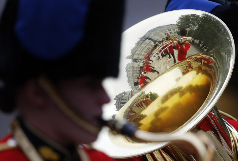 A military band is reflected in the bell of an instrument as it plays prior to the arrival of Britain's Prince Harry, to attend a service at St Paul's Cathedral to mark the 75th anniversary of Explosive Ordnance Disposal across the British Armed Forces in London, on Thursday. The British military is marking the contribution made by the armed forces bomb disposal teams. (Frank Augstein/AP)