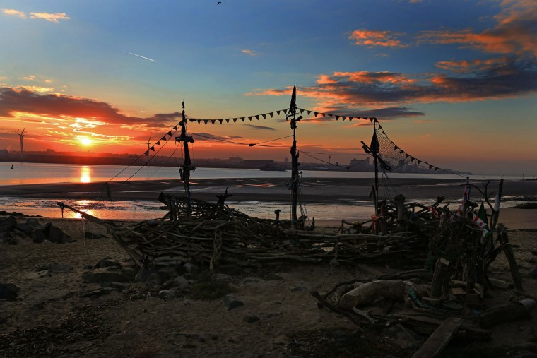 The sun rises behind a beach installation made of driftwood of the Black Pearl pirate ship on New Brighton beach, Liverpool, northwest England, Thursday, Oct. 15, 2015. The installation was created by artist Frank Lund and Major Mace. (Peter Byrne/PA via AP)