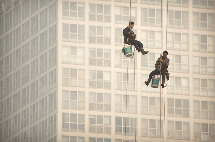 Window washers use cables to lower themselves from a skyscraper while working on a polluted day in Beijing on Tuesday. Air quality readings in the city were at levels considered hazardous by international measuring standards. (Mark Schiefelbein/AP)