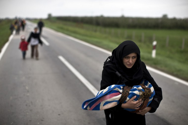 A woman carries a child as she moves on foot towards a registration center in Opatovac, Croatia, Tuesday, Oct. 20, 2015. Croatia's interior minister says his country is trying to coordinate the transfer of migrants with Slovenia, which has accused its neighbor of failing to manage the relentless flow of people. (AP Photo/Marko Drobnjakovic)