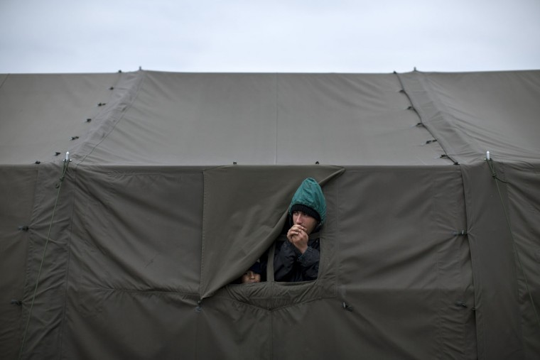 A man warms his hands as he peers out of a tent at a registration center for migrants and refugees in Opatovac, Croatia, Tuesday, Oct. 20, 2015. Croatia's interior minister says his country is trying to coordinate the transfer of migrants with Slovenia, which has accused its neighbor of failing to manage the relentless flow of people. (AP Photo/Marko Drobnjakovic)