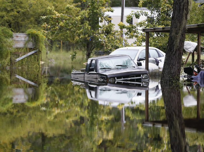 Floodwater surrounds cars parked behind a home in Ridgeville, S.C. Despite an improving forecast, it will still take weeks for the state to return to normal after being pummeled by a historic rainstorm. (John Bazemore/AP)