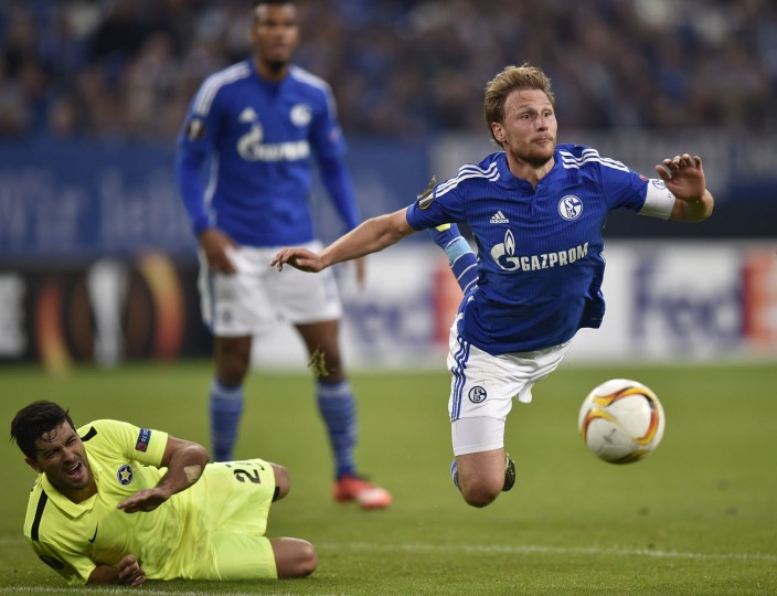 Asteras' Braian Lluy watches Schalke's Benedikt Hoewedes, right, jumping for the ball during the Europa League group K soccer match between FC Schalke 04 and Asteras Tripolis FC in Gelsenkirchen, Germany, Thursday, Oct. 1, 2015. (AP Photo/Martin Meissner)