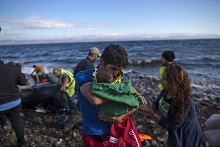 A Syrian refugee man holds a child after arriving on a dinghy from the Turkish coast to the northeastern Greek island of Lesbos, Thursday, Oct. 1, 2015. The International Organization for Migration says a record number of people have crossed the Mediterranean into Europe this year. (AP Photo/Muhammed Muheisen)