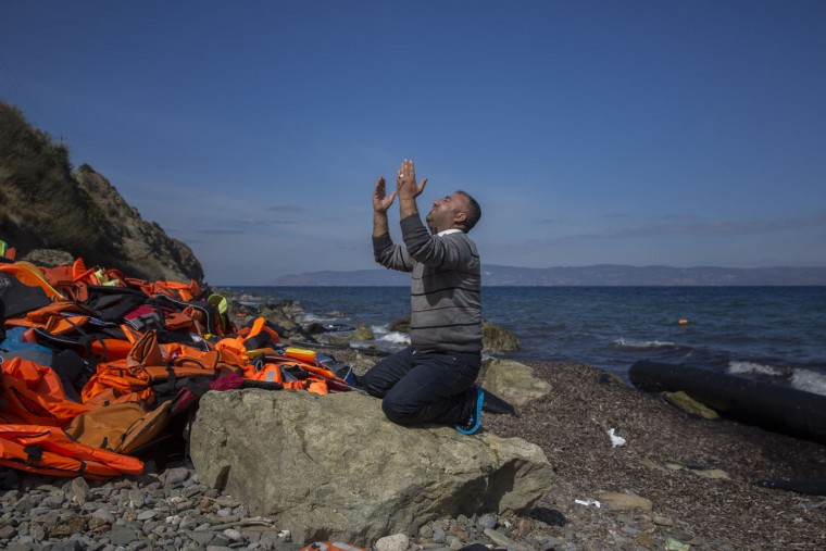 A refugee prays shortly after he and other migrants arrived on a dinghy from the Turkish coast to the northeastern Greek island of Lesbos, Thursday, Oct. 1, 2015 The International Organization for Migration says a record number of people have crossed the Mediterranean into Europe this year, now topping a half a million as some 388,000 have entered via Greece. (AP Photo/Santi Palacios)