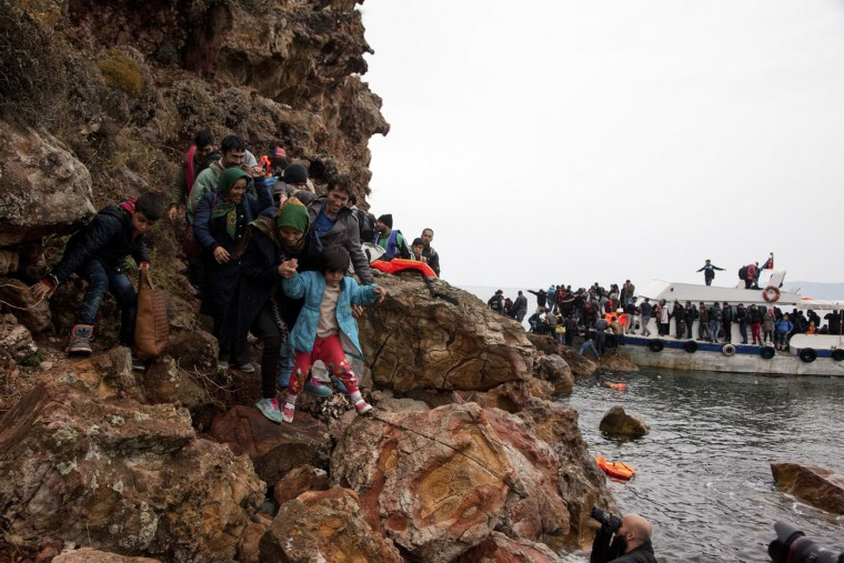 "Migrants try to make their way on rocks after their arrival by boat, on the eastern Aegean island of Lesbos, Greece, Sunday Oct. 11, 2015. Greece's first ""hotspot,"" or migrant processing center, will open over the next 10 days, allowing migrants to be flown to other European Union countries, mostly of their preference, and have their asylum applications processed there, European Union officials say. (AP Photo/Antonis Pasvantis)"