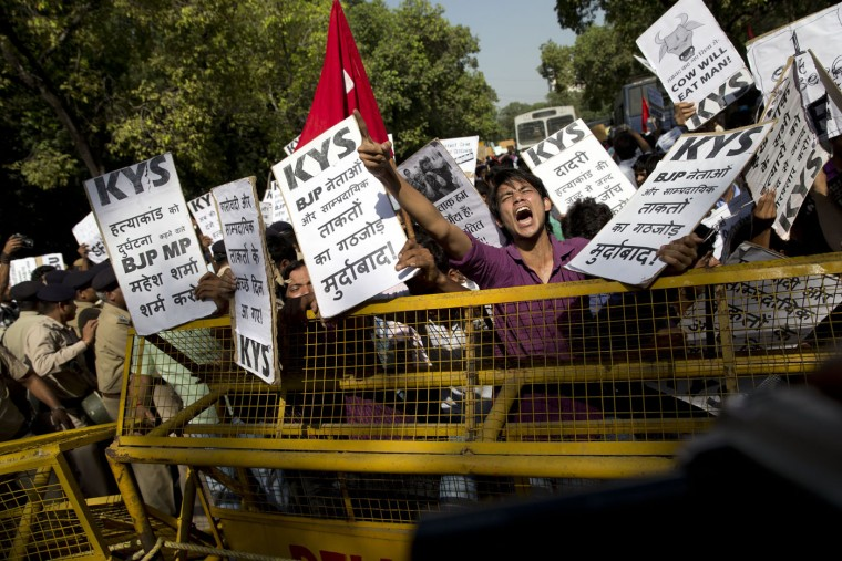 "A Krantikari Yuva Sangathan (KYS) activist shouts slogans during a protest against the killing of a 52-year-old Muslim farmer Mohammad Akhlaq, in New Delhi, India, Sunday, Oct. 11, 2015. A few days ago Indian villagers allegedly beat Akhlaq to death and severely injured his son upon hearing rumors that the family was eating beef, a taboo for many among India's majority Hindu population. The incident happened in Bisara, a village about 45 kilometers (25 miles) southeast of the Indian capital of New Delhi. Placards read, foreground, ""Down with Ministers and Sectarians of India's ruling Bharatiya Janata Party (BJP)"", left, ""Shame on Mahesh Sharma, a BJP member of parliament, who called the murder as accident"". (AP Photo /Tsering Topgyal)"