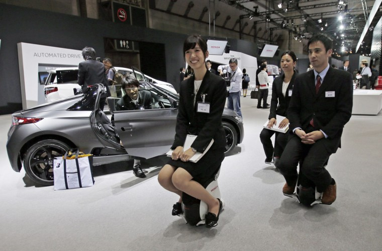 Honda Motor Co. employees ride on Honda UNI-CUB fl through the Japanese automaker's booth during the media preview of the Tokyo Motor Show in Tokyo Wednesday, Oct. 28, 2015. The biennial exhibition of vehicles in Japan runs for the public from Friday, Oct. 30. (AP Photo/Shuji Kajiyama)