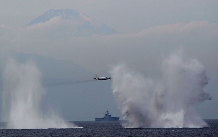 Japanese Maritime Self-Defense Force's P3C anti-submarine patrol plane flies low after dropping anti-submarine bombs during an event held ahead of Sunday's official triennial Maritime Self-Defense Force fleet review off Sagami Bay, south of Tokyo, Japan, Thursday, Oct. 15, 2015. A fleet of Japanese navy vessels sailed Sagami Bay on Thursday in a show of display of the navy's destroyers, submarines and aircraft. (AP Photo/Koji Ueda)