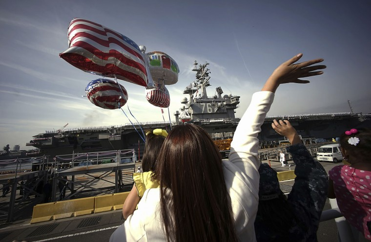 Family members of the crews of U.S. navy nuclear-powered aircraft carrier USS Ronald Reagan wave upon arrival at the U.S. Navy's Yokosuka base in Yokosuka, south of Tokyo Thursday, Oct. 1, 2015. The USS Ronald Reagan has entered its new home in Japan's Yokosuka naval port, replacing its predecessor USS George Washington. The arrival Thursday comes as Tokyo tries to deepen defense ties with the U.S. under new security law that expand the role of Japan's military. (AP Photo/Eugene Hoshiko)