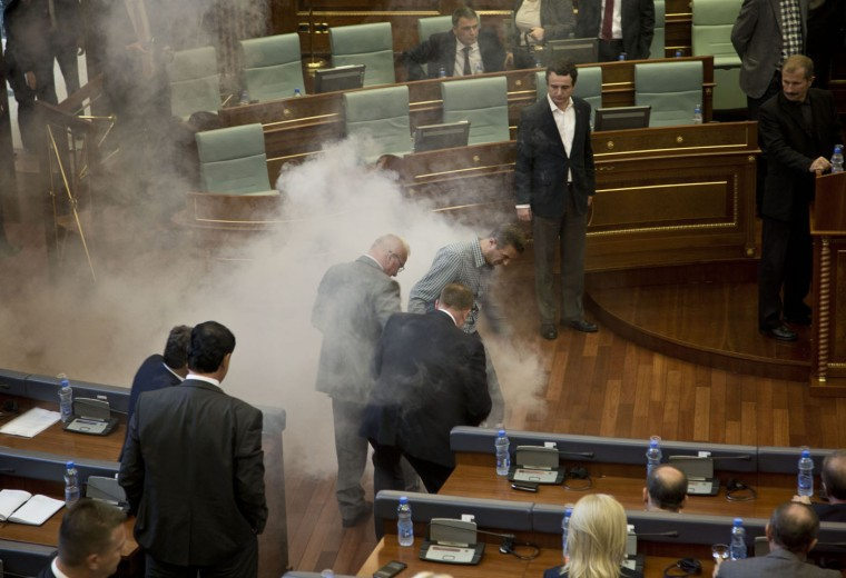 Lawmakers try to move a tear gas canister thrown by opposition lawmakers in Kosovo, disrupting Parliament's session, in the capital Pristina, Thursday, Oct. 15, 2015. The opposition protested over the government's recent EU-sponsored deal with Serbia giving the country's Serb-majority areas greater powers. (AP Photo/Visar Kryeziu)