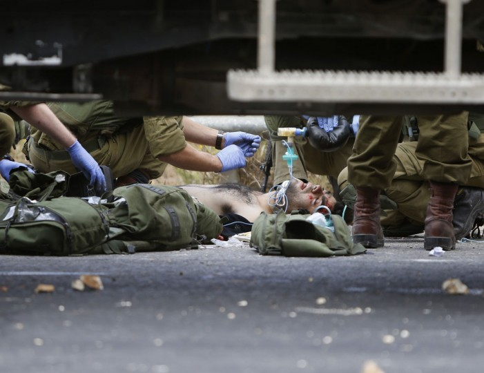 """Israeli soldiers treat Palestinians wounded during clashes between Palestinians and Israeli military forces, near Ramallah, West Bank, Wednesday, Oct. 7, 2015. Israel's prime minister says he is calling off a planned trip to Germany because of a wave of violence between Israelis and Palestinians. A statement from Benjamin Netanyahu's office Wednesday said the Israeli leader would not depart for the two-day visit so that he could """"closely monitor the situation."""" (AP Photo/Majdi Mohammed)"""