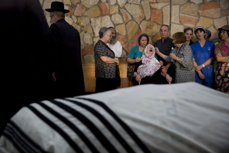 Iza Gobberg, center, reacts during her son Alon Gobberg's funeral in Jerusalem, Wednesday, Oct. 14, 2015. On Tuesday, a pair of Palestinian men boarded a bus in Jerusalem and began shooting and stabbing passengers. Two Israelis including Gobberg and two attackers were killed. (AP Photo/Oded Balilty)