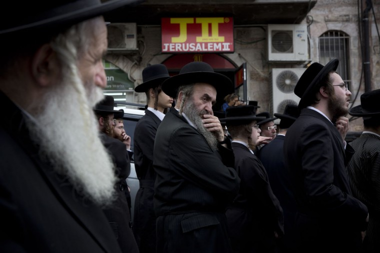 Ultra-Orthodox Jewish men gather around the body of Yeshayahu Kirshavski during his funeral in Jerusalem, Tuesday, Oct. 13, 2015. A pair of Palestinian men boarded a bus in Jerusalem and began shooting and stabbing passengers, while another assailant rammed a car into a bus station before stabbing bystanders, in near-simultaneous attacks Tuesday that escalated a monthlong wave of violence. Three Israelis and two attackers were killed. (AP Photo/Oded Balilty)
