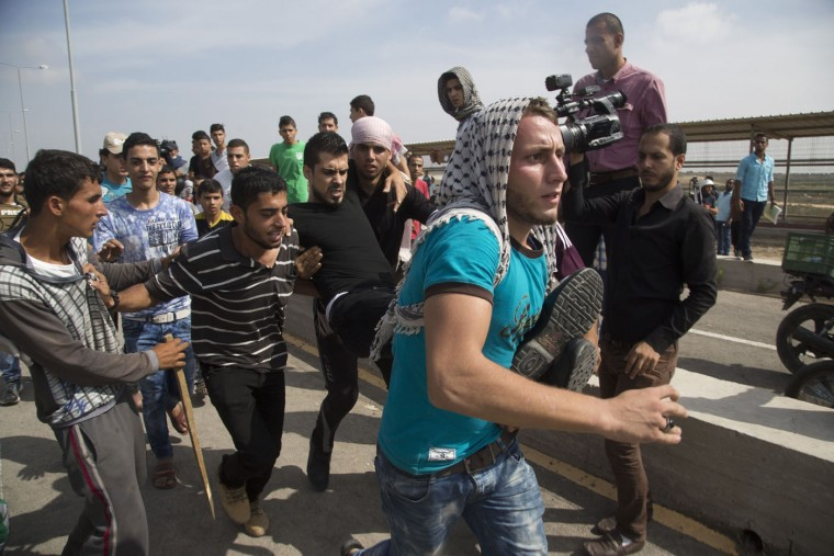 Palestinians carry a wounded man during clashes with Israeli soldiers at the entrance of Erez border crossing between Gaza Strip and Israel, in the northern Gaza Strip, Tuesday, Oct. 13, 2015. Recent days have seen a series of stabbing attacks in Israel and the West Bank that have wounded several Israelis. Past weeks have also seen violent demonstrations in the West Bank and Gaza. (AP Photo/Adel Hana)