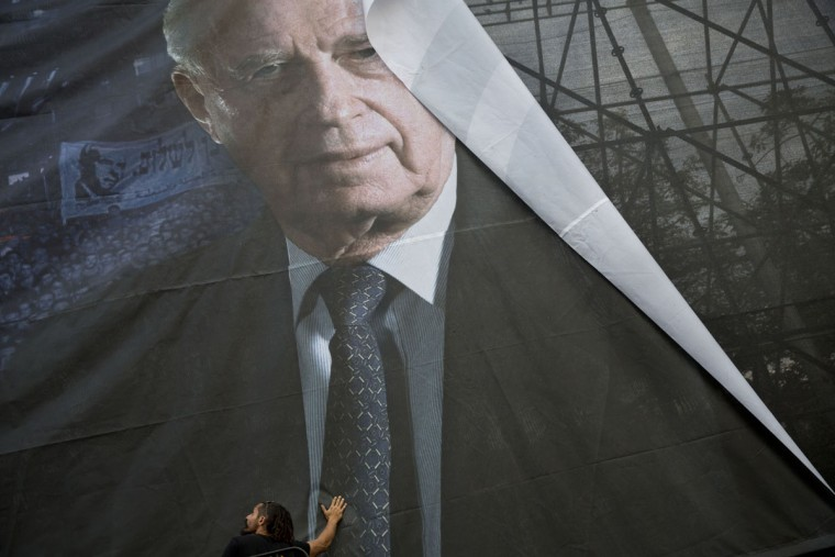 Israeli workers hang up a billboard with the portrait of late Israeli Prime Minister Yitzhak Rabin, ahead of a memorial rally for the 20th anniversary of his assassination at Rabin square in Tel Aviv, Israel, Wednesday, Oct. 28, 2015. In 1995, Rabin was assassinated by a right-wing Israeli minutes after attending a festive peace rally. (AP Photo/Oded Balilty)