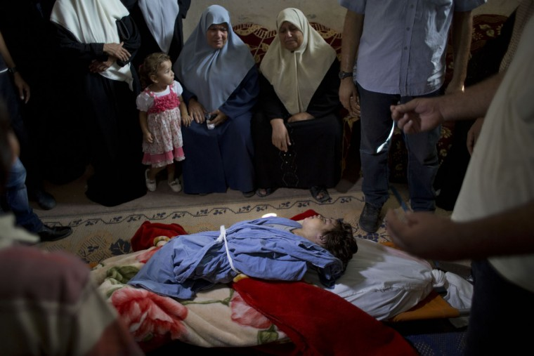 Palestinian mourners weep over the bodies of two-year-old Rahaf Hassan and her 30-year-old pregnant mother, Noor Hassan, who were killed in an Israeli air strike Sunday morning, during their funeral in the family house south of Gaza city in the Gaza Strip, Sunday, Oct. 11, 2015. In response to renewed rocket fire toward Israel, the military said it carried out airstrikes in Gaza targeting Hamas weapons manufacturing facilities. Ashraf Al-Kidra, a Health Ministry spokesman in Gaza, said a nearby home was struck, which killed Rahaf and Noor and wounded four others including Noor's husband and son. (AP Photo/ Khalil Hamra)