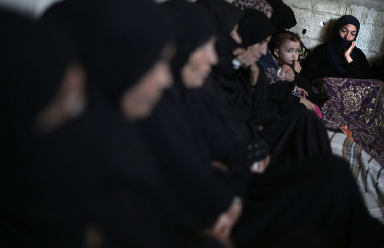Palestinian women mourn at the family house of Ahmed Al-Serhi, 27, who was killed during clashes with Israeli troops near the Israeli border with Gaza, during his funeral in Deir el-Balah, in the central Gaza Strip, Wednesday, Oct. 21, 2015. (AP Photo/ Khalil Hamra)