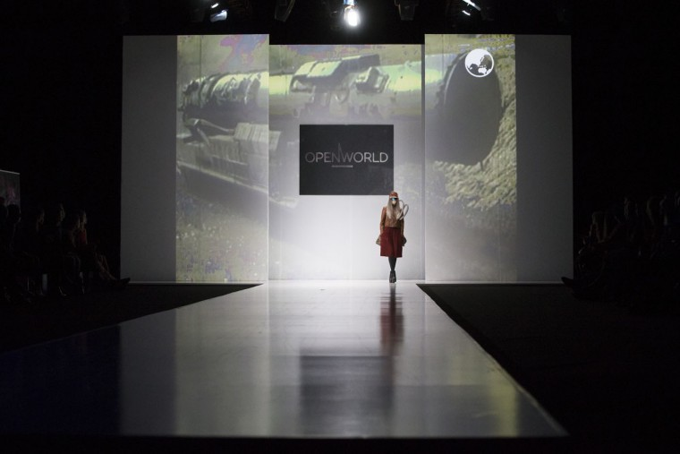 A models displays a creation by 'Open World', a group of young designers with a projection of Russian missile in the background during Fashion Week in Moscow, Russia, Thursday, Oct. 15, 2015. (AP Photo/Alexander Zemlianichenko)