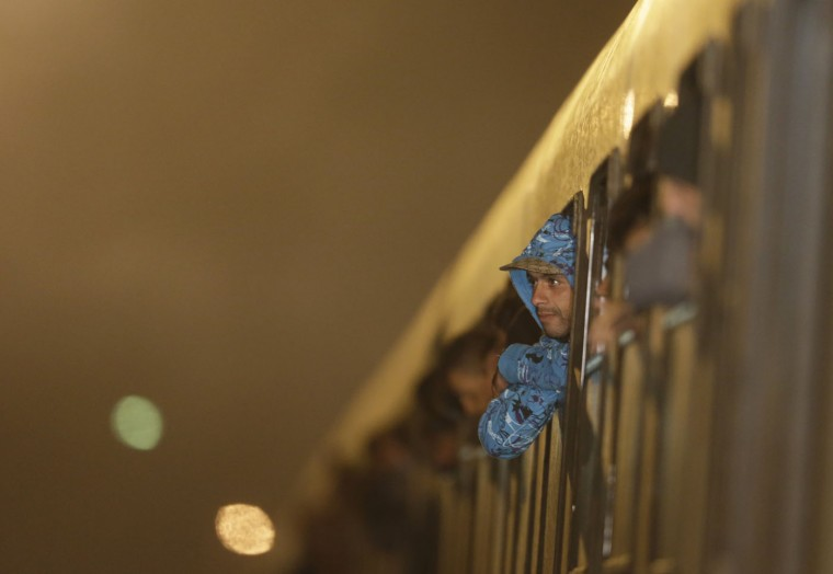 A man looks out of a window of a train carrying hundreds of migrants as it stops at the train station in Sredisce ob Dravi, Slovenia, Tuesday, Oct. 20, 2015. Hungary shut down its border with Croatia to the free flow of migrants, prompting Croatia to redirect thousands of people toward its border with Slovenia. (AP Photo/Petr David Josek)