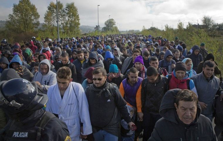 "Migrants walk towards a reception facility after crossing from Croatia, in Dobova, near a border crossing between Croatia and Slovenia Tuesday, Oct. 20, 2015. Slovenia accused Croatia on Tuesday of sending thousands of migrants toward its borders ""without control,"" ignoring requests to contain the surge, and urged the rest of the European Union to get involved in solving the crisis. (AP Photo/Darko Bandic)"