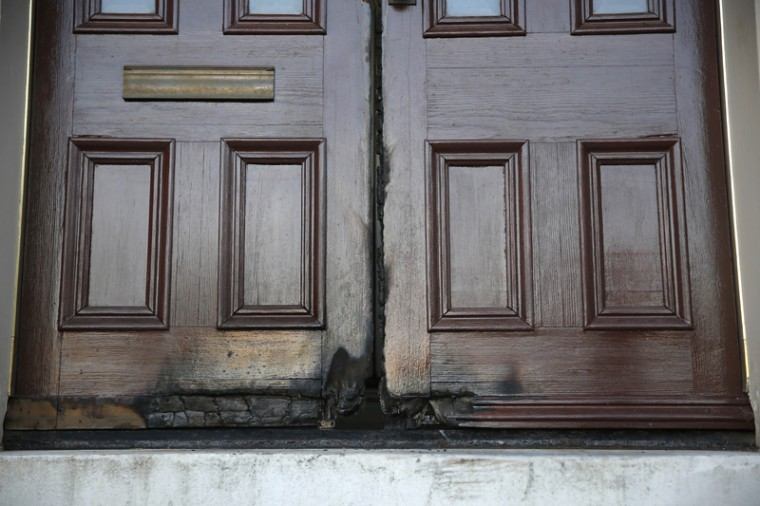 Fire-damaged rectory doors at the 173-year-old Shrine of St. Joseph church that were damaged by an arsonist are shown Thursday in St. Louis. The fire, set early Thursday morning, marks the seventh time in two weeks someone ignited doors outside a place of worship in St. Louis or one of its suburbs, police said. (Jeff Roberson/AP)