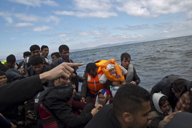 Refugees prepare to jump off a dinghy arriving from the Turkish coast to the northeastern Greek island of Lesbos, Thursday, Oct. 1, 2015. The International Organization for Migration says a record number of people have crossed the Mediterranean into Europe this year, now topping a half a million as some 388,000 have entered via Greece. (AP Photo/Muhammed Muheisen)