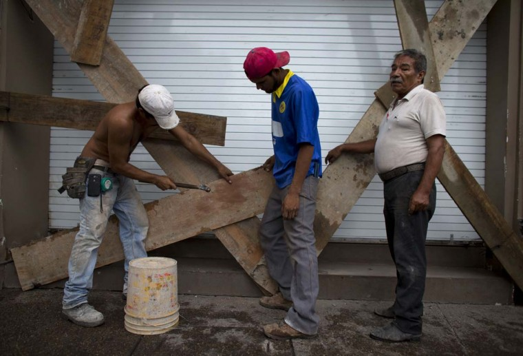 "Men nail boards across the shutters of a waterfront business, as residents prepare for the arrival of Hurricane Patricia in Puerto Vallarta, Mexico, Friday, Oct. 23, 2015. Patricia barreled toward southwestern Mexico Friday as a monster Category 5 storm, the strongest ever in the Western Hemisphere. Locals and tourists were either hunkering down or trying to make last-minute escapes ahead of what forecasters called a ""potentially catastrophic landfall"" later in the day.  