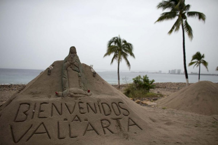 "A sand sculpture carved with a message that reads in Spanish; ""Welcome to Vallarta"" decorates the beach in Puerto Vallarta, Mexico, Friday, Oct. 23, 2015. Patricia barreled toward southwestern Mexico Friday as a monster Category 5 storm, the strongest ever in the Western Hemisphere. Locals and tourists were either hunkering down or trying to make last-minute escapes ahead of what forecasters called a ""potentially catastrophic landfall"" later in the day.  