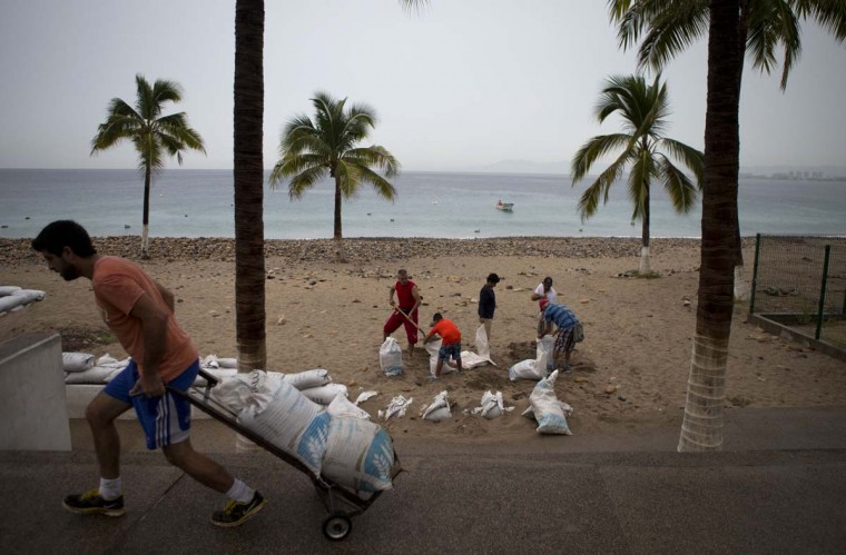 "Residents prepare for the arrival of Hurricane Patricia filling sand bags to protect beachfront businesses, in Puerto Vallarta, Mexico, Friday, Oct. 23, 2015. Patricia barreled toward southwestern Mexico Friday as a monster Category 5 storm, the strongest ever in the Western Hemisphere. Locals and tourists were either hunkering down or trying to make last-minute escapes ahead of what forecasters called a ""potentially catastrophic landfall"" later in the day.  