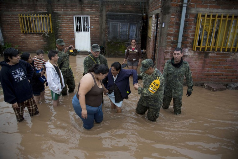 Soldiers help a woman to leave her flooded house to take her to a shelter in Zoatlan, Nayarit state, some 150 km northwest of Guadalajara,  Mexico, Saturday, Oct. 24, 2015. Hurricane Patricia made landfall Friday on a sparsely populated stretch of Mexico's Pacific coast as a Category 5 storm, avoiding direct hits on the resort city of Puerto Vallarta and major port city of Manzanillo as it weakened to tropical storm force while dumping torrential rains that authorities warned could cause deadly floods and mudslides. (AP Photo/Eduardo Verdugo)