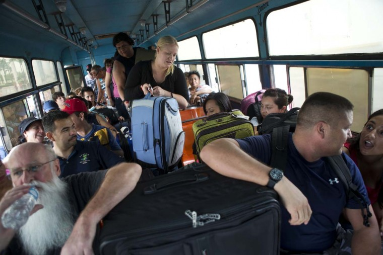Mexican and international tourists board a bus to be transported to a shelter, bracing for the arrival of Hurricane Patricia in Puerto Vallarta, Mexico, Friday, Oct. 23, 2015. Teams of police and civil protection are walking along Puerto Vallarta's waterfront, advising people to evacuate. A top civil protection official says that three airports in the path of Patricia in southwestern Mexico have been shut down as the storm approaches. (AP Photo/Rebecca Blackwell ORG XMIT: RLB114