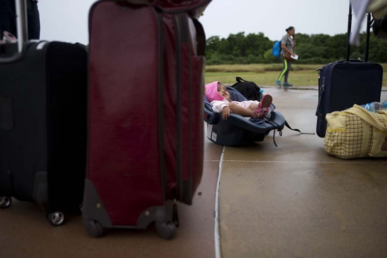 Framed by luggage, a toddler sits in a baby carrier as tourists wait for buses to transfer them from a conference center to a shelter ahead of Hurricane Patricia's arrival, in Puerto Vallarta, Mexico, Friday, Oct. 23, 2015. Teams of police and civil protection are walking along Puerto Vallarta's waterfront, advising people to evacuate. A top civil protection official says that three airports in the path of Patricia in southwestern Mexico have been shut down as the storm approaches.   || CREDIT: REBECCA BLACKWELL - AP PHOTO