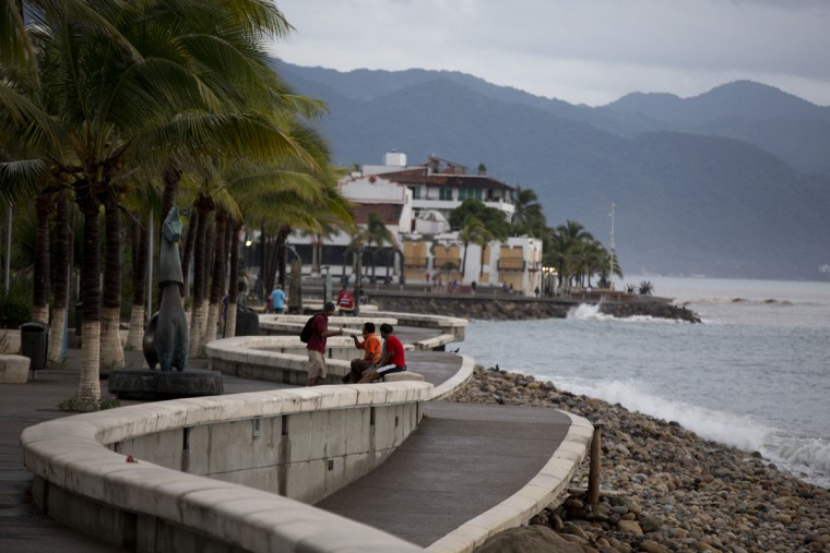 People enjoy a seafront walkway the morning after Hurricane Patricia passed further south, sparing Puerto Vallarta, Mexico, Saturday, Oct. 24, 2015. Hurricane Patricia made landfall Friday on a sparsely populated stretch of Mexico's Pacific coast as a Category 5 storm, avoiding direct hits on the resort city of Puerto Vallarta and major port city of Manzanillo as it weakened to tropical storm force while dumping torrential rains that authorities warned could cause deadly floods and mudslides.(AP Photo/Rebecca Blackwell)