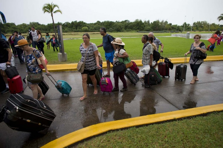 As Hurricane Patricia approaches Mexican and international tourists wait in line to board buses that will transport them to a shelter, in Puerto Vallarta, Mexico, Friday, Oct. 23, 2015. Teams of police and civil protection are walking along Puerto Vallarta's waterfront, advising people to evacuate. A top civil protection official says that three airports in the path of Patricia in southwestern Mexico have been shut down as the storm approaches.  || CREDIT: REBECCA BLACKWELL - AP PHOTO