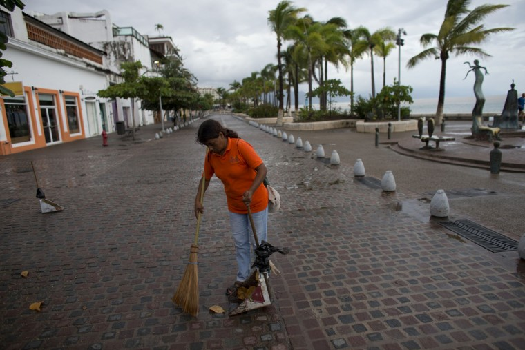 A city cleaner sweeps normal leaves and debris from a seafront walkway, the morning after Hurricane Patricia passed further south sparing Puerto Vallarta, Mexico, Saturday, Oct. 24, 2015. The storm made landfall Friday evening on Mexico's Pacific coast as a Category 5 hurricane with maximum sustained winds of 165 mph (270 kph) but it is rapidly losing steam as it moves over a mountainous region inland from the shore.(AP Photo/Rebecca Blackwell)