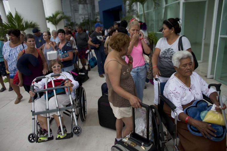 Mexican and international tourists wait at a conference center to be transferred to a shelter, ahead of the arrival of Category 5 Hurricane Patricia in Puerto Vallarta, Mexico, Friday, Oct. 23, 2015. Teams of police and civil protection are walking along Puerto Vallarta's waterfront Friday morning advising people to evacuate. A top civil protection official says that three airports in the path of Patricia in southwestern Mexico have been shut down as the storm approaches.  || CREDIT: REBECCA BLACKWELL - AP PHOTO