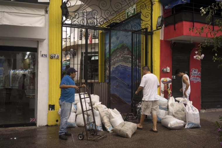 "People unload sandbags to use as protection of their businesses in preparation Hurricane Patricia in the Pacific resort city Puerto Vallarta, Mexico, Friday, Oct. 23, 2015. Patricia barreled toward southwestern Mexico Friday as a monster Category 5 storm, the strongest ever in the Western Hemisphere. Locals and tourists were either hunkering down or trying to make last-minute escapes ahead of what forecasters called a ""potentially catastrophic landfall"" later in the day.  