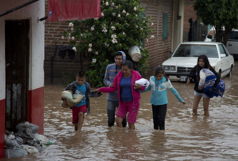 Residents walk along a flooded street in Zoatlan, Nayarit state, some 150 km northwest of Guadalajara, Mexico, Saturday, Oct. 24, 2015. Hurricane Patricia made landfall Friday on a sparsely populated stretch of Mexico's Pacific coast as a Category 5 storm, avoiding direct hits on the resort city of Puerto Vallarta and major port city of Manzanillo as it weakened to tropical storm force while dumping torrential rains that authorities warned could cause deadly floods and mudslides. (AP Photo/Eduardo Verdugo)
