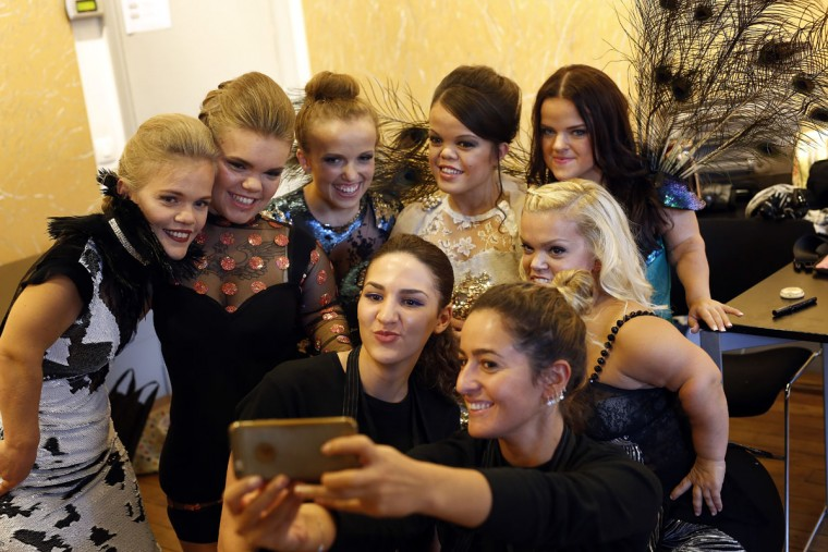 Models pose for a selfie before hitting the catwalk at the French Ministry of Culture during the dwarf fashion show in Paris, France, Friday Oct. 2, 2015. The dwarf fashion show is an event organizers say is aimed at highlighting the elitism and prejudice that the model industry encourages in its depiction of bodies. It is presented during the Paris Fashion Week but is not part of it. (AP Photo/Jerome Delay)