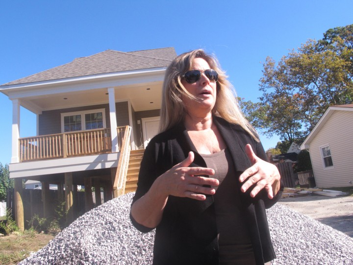In this Oct. 12, 2015 photo, Michelle Petrow stands in front of her unfinished home in Manasquan, N.J. Three years after Superstorm Sandy destroyed her old home, she is still not able to move in to a rebuilt one because it has not been completed. (AP Photo/Wayne Parry)