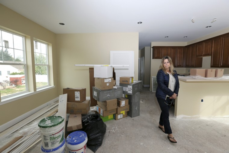 In this Saturday, Oct. 24, 2015, photo, Michelle Petrow looks at building materials in her home, three years after Superstorm Sandy, in Manasquan, N.J. The single mother of three, who needs a kidney transplant, is still rebuilding after years of fighting with insurers, contractors and state aid programs. But she's not even sure she'll be able to move in to the new home rising 15 feet higher than her old one: her bank is foreclosing on it because she stopped making payments for a year and a half while she simultaneously rented an apartment. (AP Photo/Mel Evans)