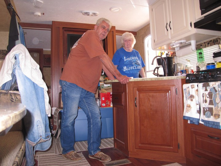 In this Oct. 21, 2015 photo, Bob Collis, left, and his wife, Katherine, right, stand in their trailer in Berkeley Township, N.J. They have been unable to return to their home in Toms River, N.J., since Superstorm Sandy damaged it three years ago. (AP Photo/Wayne Parry)