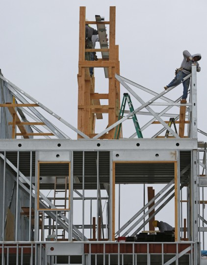 """Construction workers build the framework for a house near the beach in Belle Harbor before the third anniversary of Superstorm Sandy, Tuesday, Oct. 27, 2015, in New York. Homes closest to the Atlantic Ecean were heavily damaged by storm surge and floodwaters from the """"hundred-year storm."""" (AP Photo/Kathy Willens)"""
