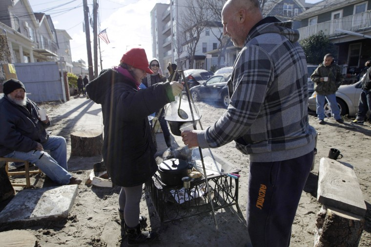 FILE - In this Nov. 3, 2012, file photo, Kiva Kahl pours hot tea for neighbor Buddy Sammis, right, after she prepared it on a wood-stoked fire and cooking setup she and her fiance created in the street in front of their house on Beach 91st Street in the Rockaways in New York. Rebuilding is still taking place three years since Superstorm Sandy, for instance along the Rockaway Beach boardwalk, and includes walls to provide better protection against the surf. (AP Photo/Kathy Willens, File)